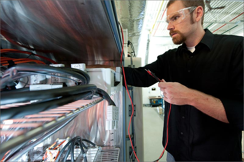 NREL's Jeremy Neubauer measures battery voltage in an environmental chamber at the Thermal Test Facility. NREL is identifying battery second use (B2U) strategies capable of offsetting vehicle expenses while improving utility grid stability. Photo by Dennis Schroeder
